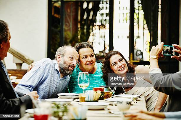 Grandmother embracing children for photo at dinner