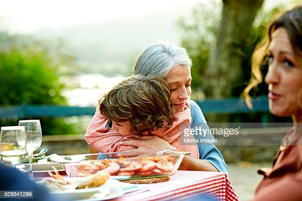 Grandmother embracing grandson at outdoor table