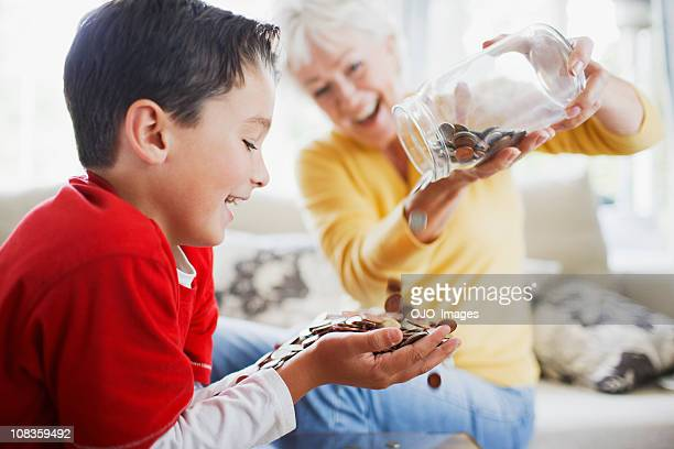 Grandmother emptying jar of coins into grandsons hands