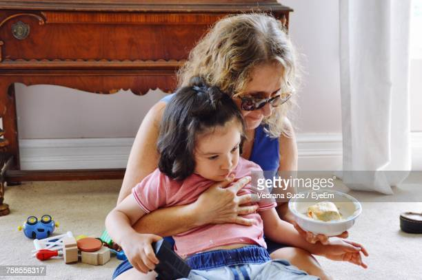 Grandmother Feeding Granddaughter While Sitting At Home