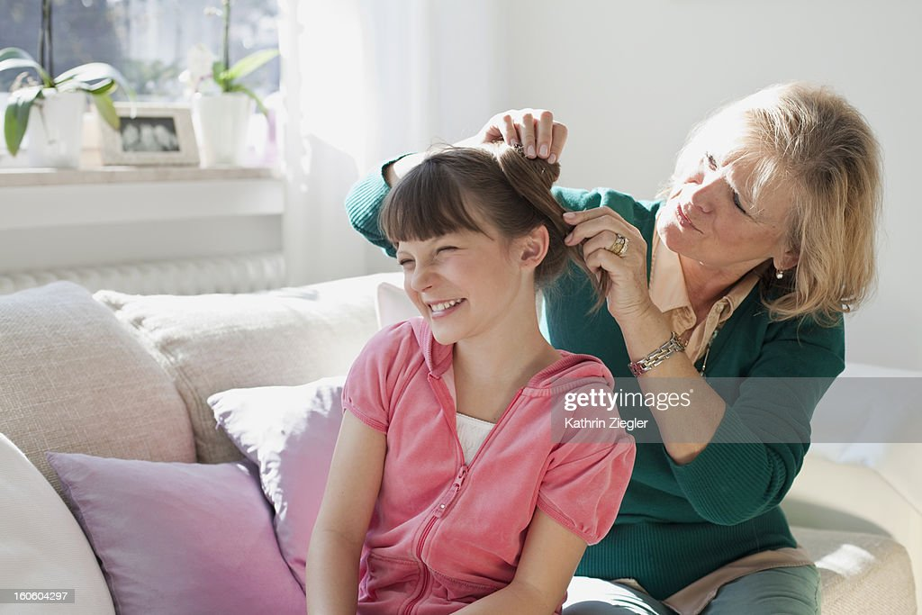 grandmother fixing granddaughter's hair : Stock Photo