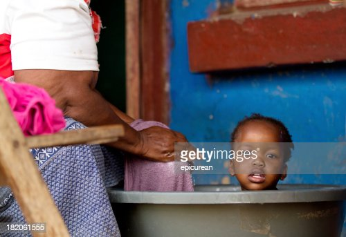 Grandmother gives her granddaughter a bath in rural South Africa