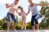 Grandmother, Granddaughter And Mother Bouncing On Trampoline Smiling To Camera