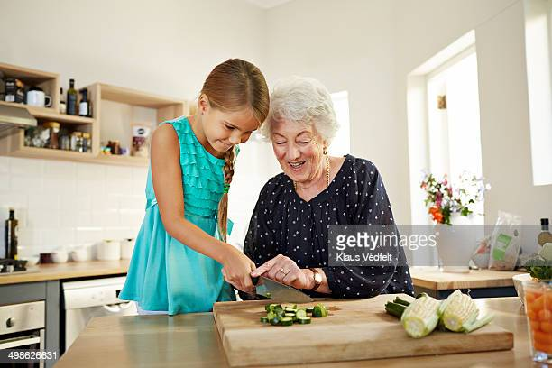Grandmother helping girl with chopping veg