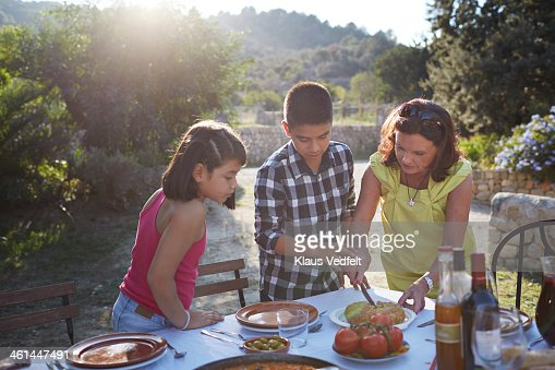 Grandmother helping grandchildren with food