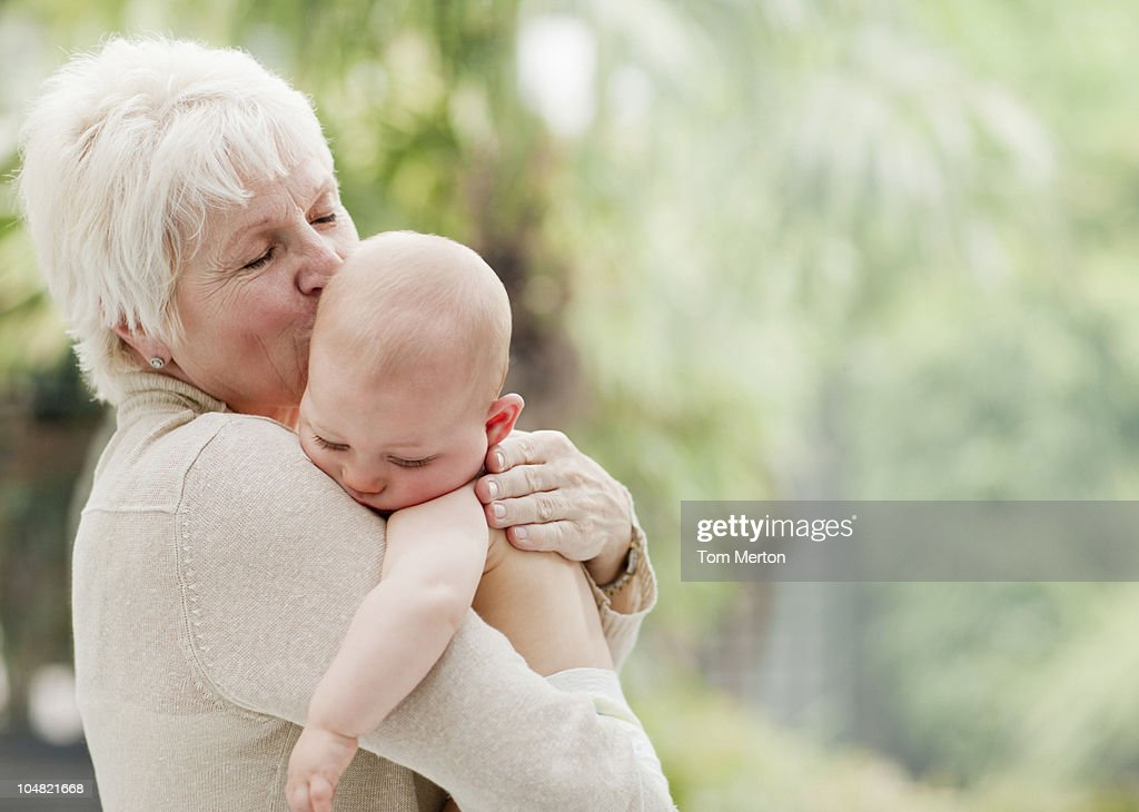 Grandmother holding and kissing baby : Stock Photo