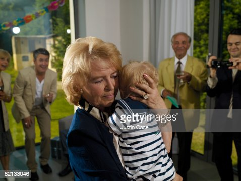 Grandmother holding baby at family party : Stock Photo