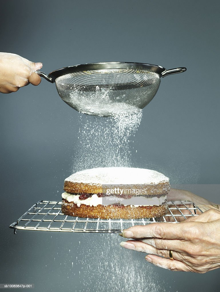 Grandmother holding cake granddaughter (6-7) sieving sugar, close-up : Stock Photo