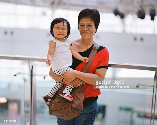 Grandmother holding cheerful baby joyfully