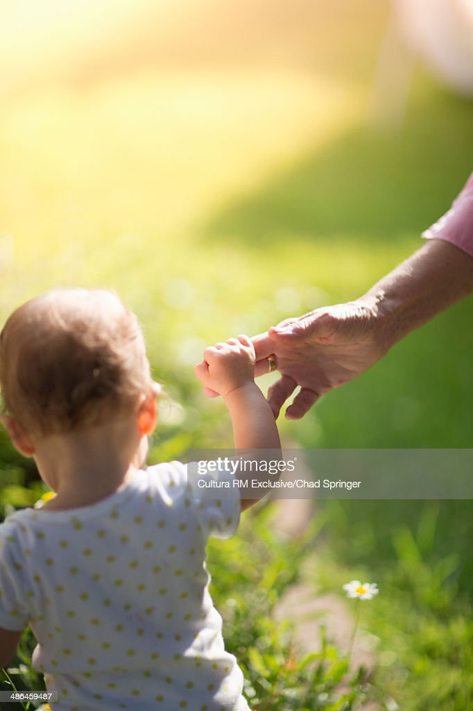 Grandmother holding granddaughter's hand