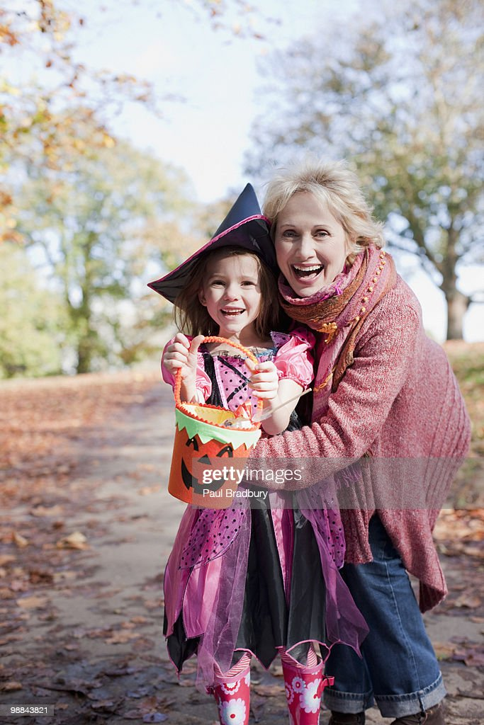 Grandmother hugging granddaughter in Halloween costume : Stock Photo