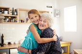Grandmother hugging granddaughter in kitchen