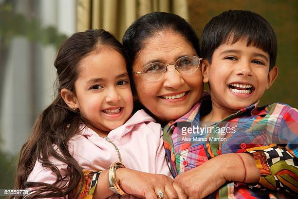 grandmother hugs grandkids, all smile at camera