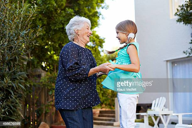 Grandmother jumping with grandchild in garden