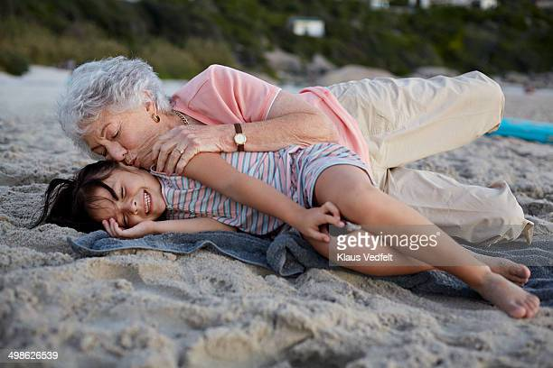 Grandmother kissing girl on the cheek at beach