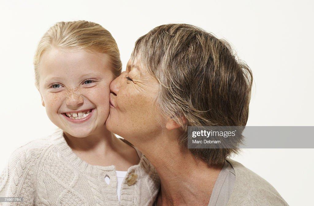 Grandmother kissing granddaughter (7-9), smiling