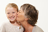 Grandmother kissing granddaughter (7-9), smiling