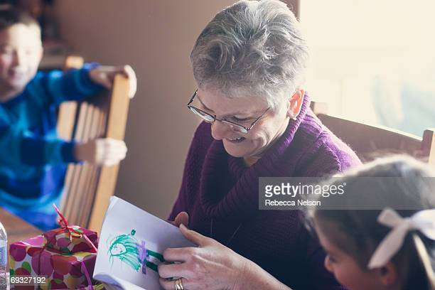 Grandmother looking at her granddaughter's drawing