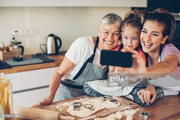 Grand-mère, mère et une fille faire selfie dans la cuisine