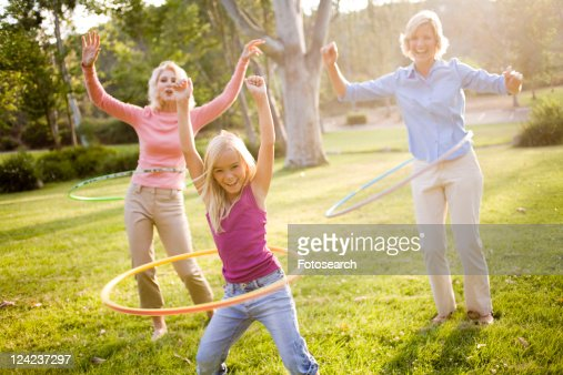 Grandmother, mother and daughter in park with hula hoops