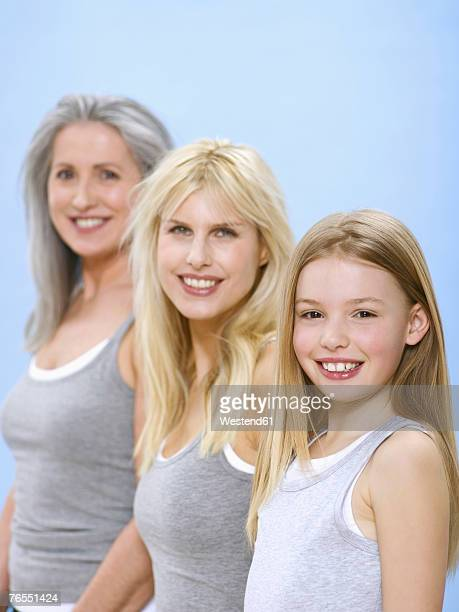 Mother daughter (10-11) and grandmother standing in row, smiling, portrait