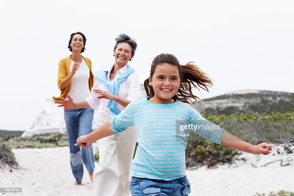 Grandmother, Mother and Granddaughter Running to Beach