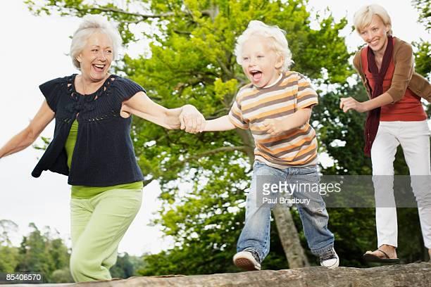 Grand-mère, mère et fils courir dans le parc