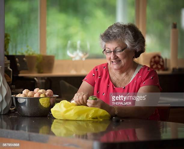 Grandmother peeling fruit for a dessert