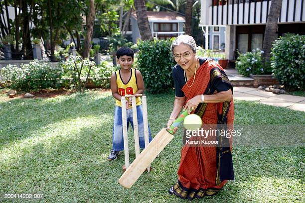 Grandmother playing cricket with grandson (6-8) batting ball, smiling