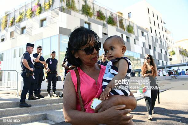 A grandmother poses on July 16 2016 in front of Pasteur hospital in Nice southern France holding her grandson who was tracked down through Facebook...