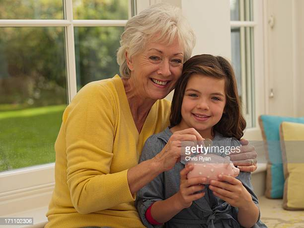 Grandmother putting coin into granddaughter's piggy bank