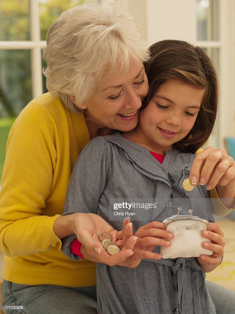 Grandmother putting coin into granddaughter's piggy bank : Stock Photo