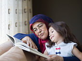 Grandmother wearing a head scarf reading book with granddaughter