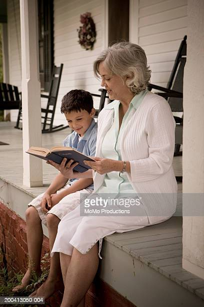 Grandmother reading book to grandson (8-10) porch