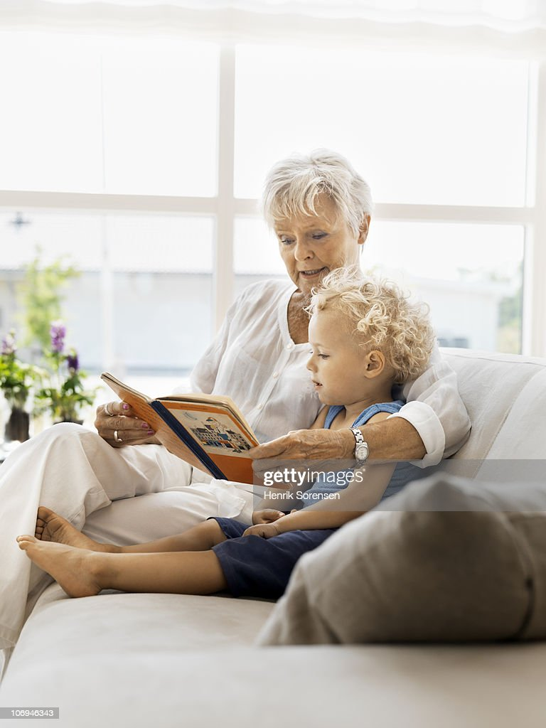 Grandmother reading loud for grandson : Stock Photo
