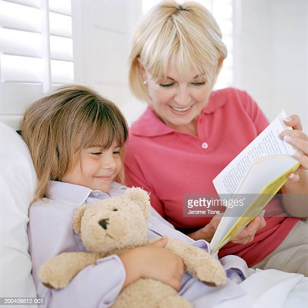 Grandmother reading to granddaughter (4-6) in bed