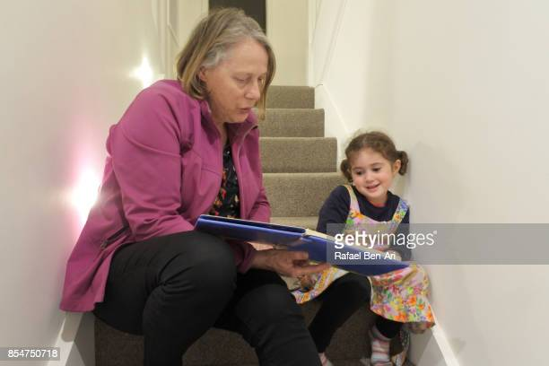 Grandmother reads a book for her granddaughter
