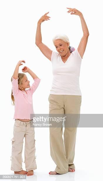 Grandmother showing granddaughter (5-7) ballet position