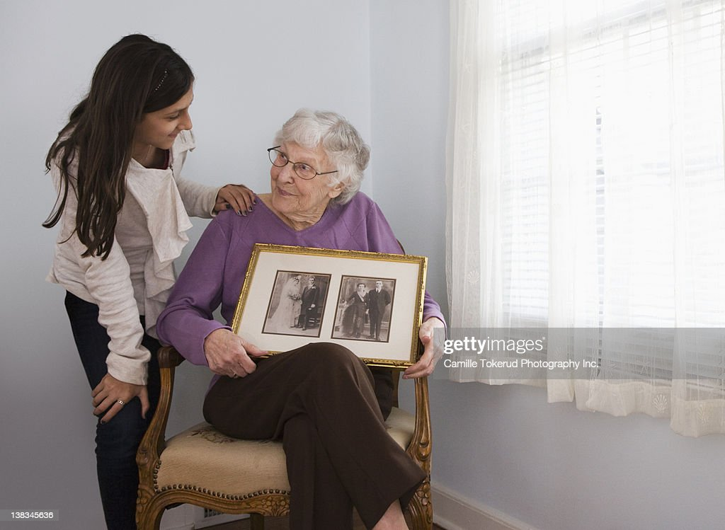 Grandmother showing granddaughter old photos : Stock Photo