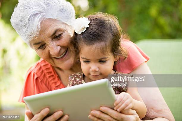Grandmother showing tablet to grandchild