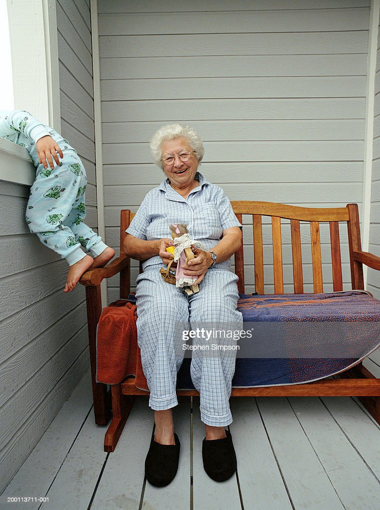 Grandmother Sitting On Balcony Granddaughter Leaning On