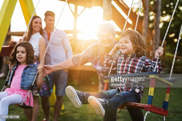 Grandmother swinging her grandchildren at sunset.