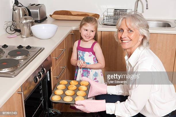 Grandmother taking cupcakes out of oven