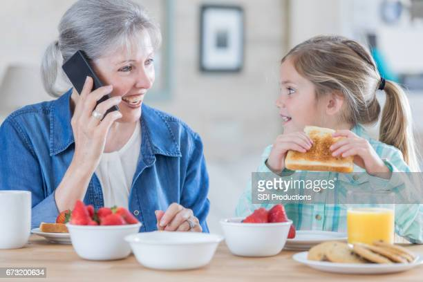 Grandmother talks on phone while smiling at granddaughter