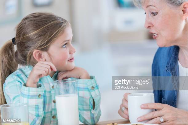 Grandmother talks with granddaughter at home