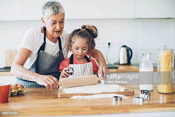 Grandmother teaching a girl to make cookies
