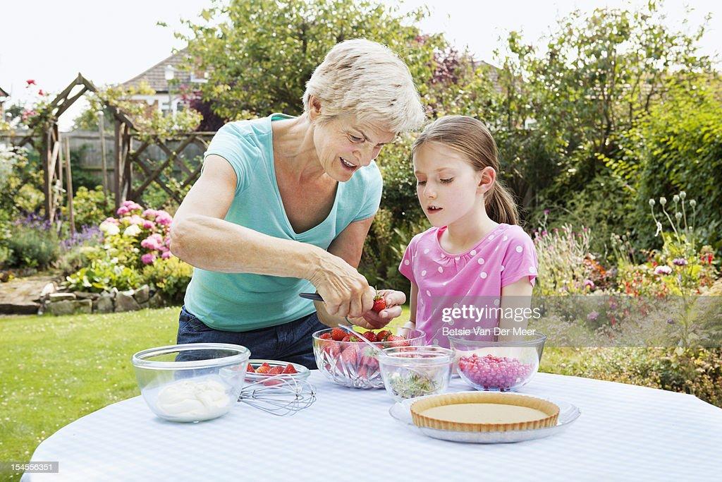 Grandmother teaching child to prepare strawberries : Stock Photo