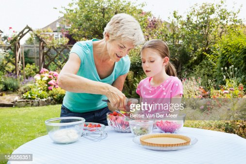 Grandmother teaching child to prepare strawberries : Stock Photo