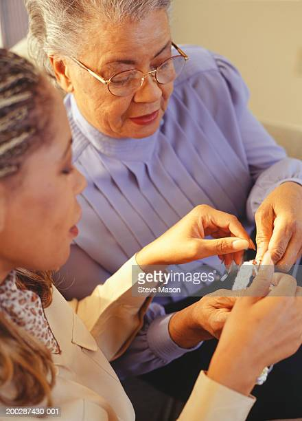 Grandmother teaching granddaughter to crochet, elevated view