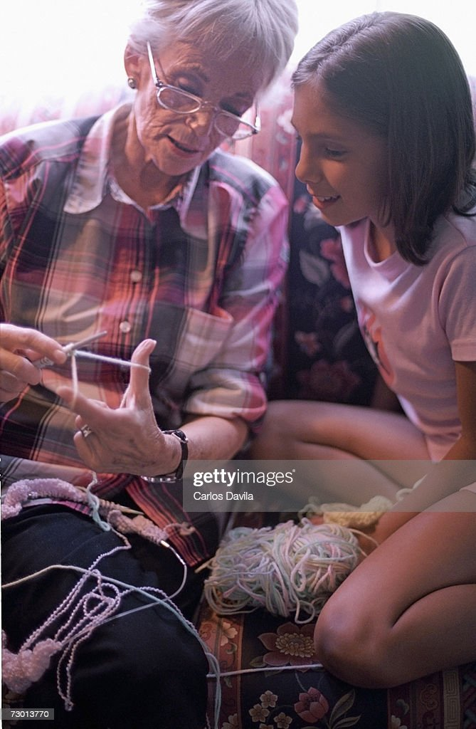 Grandmother teaching granddaughter (10-11) to crochet : Stock Photo